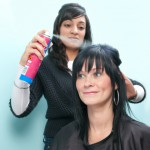 Hair stylist sprays customer's hair
